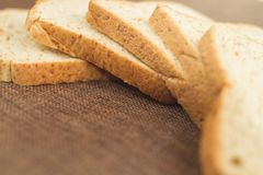 Pile slice of whole wheat bread on dark brown calico. stock image