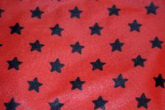 Close-up texture of a red fabric with black stars Stock Photo