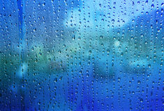 Close up texture of water drop background on blue mirror use as Stock Photos