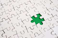 Close-up texture of a white jigsaw puzzle in assembled state with missing elements forming a green pad for text. Copy space.  Stock Photo