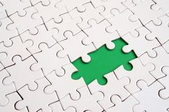 Close-up texture of a white jigsaw puzzle in assembled state with missing elements forming a green pad for text. Copy space.  Stock Photography