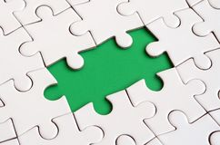 Close-up texture of a white jigsaw puzzle in assembled state with missing elements forming a green pad for text. Copy space.  Royalty Free Stock Image