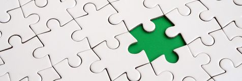 Close-up texture of a white jigsaw puzzle in assembled state with missing elements forming a green pad for text. Copy space.  Royalty Free Stock Photography