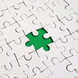 Close-up texture of a white jigsaw puzzle in assembled state with missing elements forming a green pad for text. Copy space.  Royalty Free Stock Images