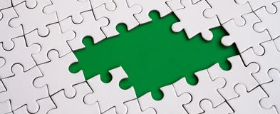 Close-up texture of a white jigsaw puzzle in assembled state with missing elements forming a green pad for text. Copy space.  Stock Images