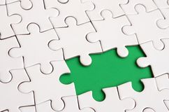 Close-up texture of a white jigsaw puzzle in assembled state with missing elements forming a green pad for text. Copy space.  Stock Photos
