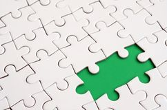 Close-up texture of a white jigsaw puzzle in assembled state with missing elements forming a green pad for text. Copy space.  Stock Image