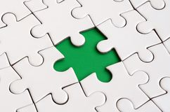 Close-up texture of a white jigsaw puzzle in assembled state with missing elements forming a green pad for text. Copy space.  Royalty Free Stock Photos