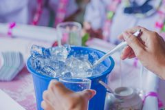 Close-up th hands add ice to the glass to distribute to friends royalty free stock photo