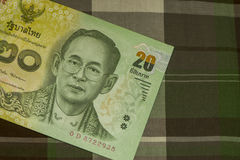 Close up of Thai banknote Thai bath with the image of Thai King. Thai banknote of 20 Thai baht on Green Scottish fabric. Royalty Free Stock Image
