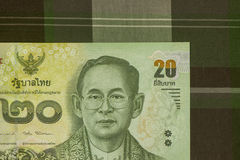 Close up of Thai banknote Thai bath with the image of Thai King. Thai banknote of 20 Thai baht on Green Scottish fabric. stock image