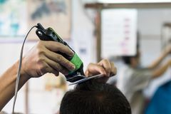 Clipper with comb, hair trimmer. Close-up of a Thai man with a barber using clippers with black hair comb in a shop royalty free stock photography