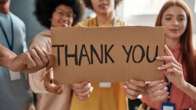 Close up of Thank you inscription, Group of diverse young volunteers looking at camera, holding card with lettering