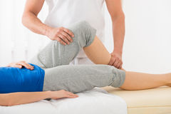 Close-up Of Therapist Doing Knee Massage Stock Photo