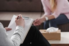 Close-up of therapist hand writing notes during a counseling session with a single woman sitting on a couch in the blurred