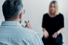 Close-up of a therapist holding a pen and talking. To his blurred female patient royalty free stock image