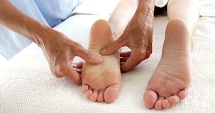 Close up of therapist massaging the feet of her patient stock video footage