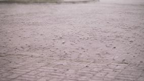 Close-up, there is heavy rain, a shower, large heavy drops drip onto the street tiles. rain drop on wet floor texture. Heavy rain drops on asphalt. puddles of stock footage