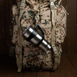 Close up of the thermos mug in the backpack side pocket on wooden table Royalty Free Stock Photo