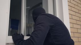 Close-up of the thief in black clothes and balaclava breaking into the house through the window. Concept of offense. Close-up of the thief in black clothes and stock video