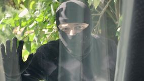 Close-up of the thief in black clothes and balaclava looking in the window preparing to break into the house. Concept of. Offense against the law, crime stock video
