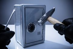 Thief Using Screwdriver And Hammer To Open Safe royalty free stock photo