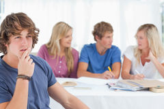 Close up of a thinking man sitting in front of his friends Stock Photography