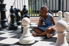 Close up of thoughtful girl sitting by chess pieces Royalty Free Stock Photography