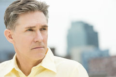 Close-Up Of Thoughtful Mature Man Looking Away. With buildings in background Royalty Free Stock Images