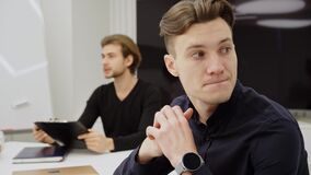 Close-up of thoughtful nervous man sitting in office with blurred positive colleague talking at background. Portrait of
