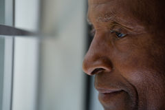 Close up of thoughtful senior man looking out through window Royalty Free Stock Image
