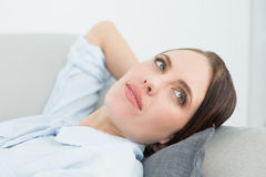 Close up of a thoughtful woman relaxing on sofa Stock Image