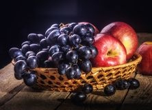 Still life with apples and grapes. Black grapes and red apples on the table in the basket Stock Images