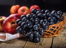 Still life with apples and grapes. Black grapes and red apples on the table in the basket Royalty Free Stock Photo