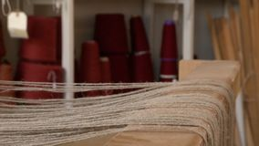 Threads on a loom ready to be woven. Close up of threads on a loom ready to be woven into cloth, with colorful thread on cones on shelves in the background stock footage