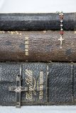Close Up Three Antique Bibles and Crosses on White Background. Close up of three antique stacked leather Bibles with antique rosary and cross made of metal wood royalty free stock photo