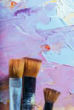 Close up of three brushes and colorful canvas Royalty Free Stock Photos