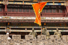 Close-up of Three Chinese Clay Soldiers. Behind a brick battlement, three clay soldiers in full regalia stand tall to guard the colorful temple behind them Royalty Free Stock Photos