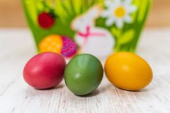 Three colorful Easter eggs in front of felt Easter basket with wooden background stock image