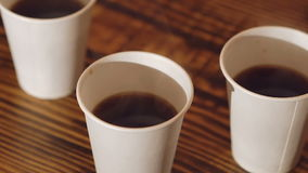 Close up of three cups of delicious coffee on the wooden table stock video