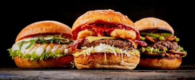Close-up of three different hamburgers on table. Close-up of three different tasty hamburgers with fish, beef meat or cheese on a wooden table against black Royalty Free Stock Image