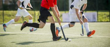 Close up of three field hockey players, challenging eachother for the control and posession of the ball during an intense, competi. Tive match on professional royalty free stock image
