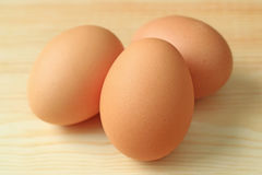 Close-up of Three fresh uncooked hen eggs on the wooden table. Background stock images
