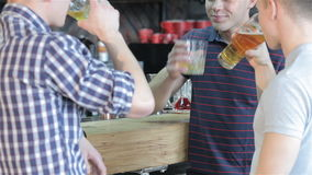 Close up of three friends drinking beverages at the bar. Close up of three male friends drinking alcoholic drinks at the bar. Two brunette guys leaning on bar stock video footage