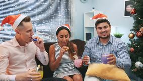 Close up of three friends in Santa hats making cheers and blowing party whistles. They have fun celebrating holidays together. Elements of this image furnished stock footage