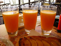 Close-up three glasses with fresh orange juice on a table. Concept of detox, healthy eating, summer. Three glasses with fresh orange juice on a table at an Royalty Free Stock Photos