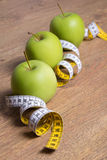 Close up of three green apples and measure tape on table Stock Image