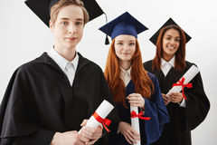 Close up of three happy mixed race international college graduates smiling rejoicing holding diplomas over white Royalty Free Stock Images