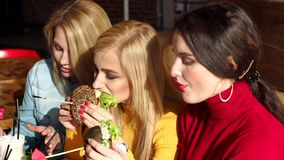 Close-up of three happy young girls having fun eating big burgers in a cafe. stock footage