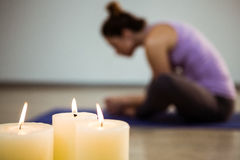 Close-up of three lit candles. And blurred woman exercising in background Royalty Free Stock Photos